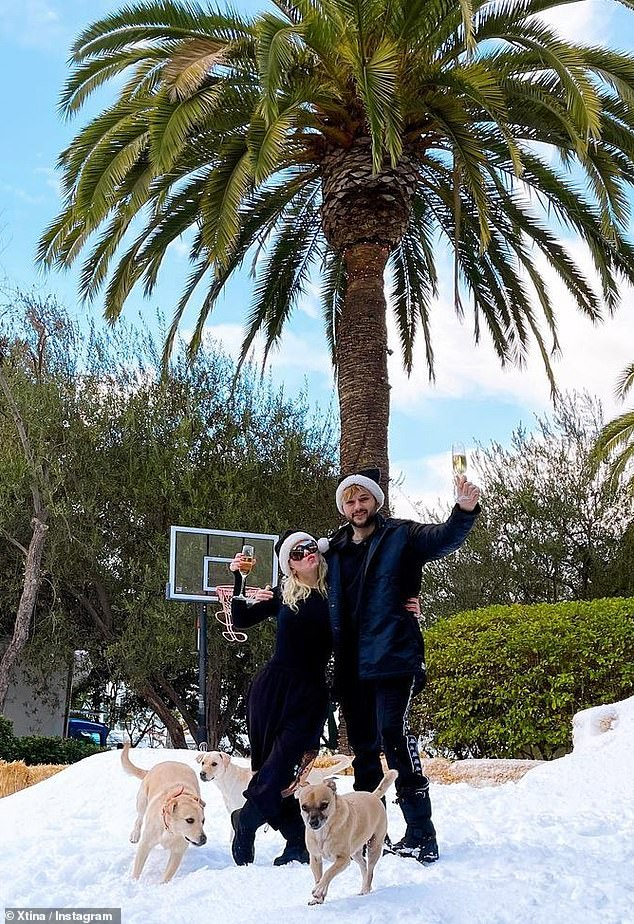 White Christmas: She and Rutler lifted some champagne glasses, as they snapped a photo on the fresh grass, swinging in identical black Santa hats