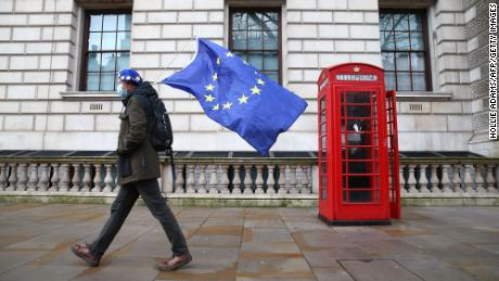 A man wearing a hat bearing the European Union flag and carrying the European Union flag is seen in Whitehall, central London, on December 11, 2020.