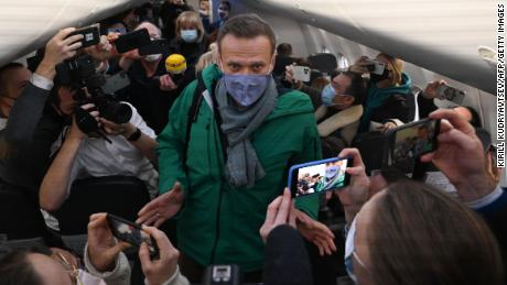 Passengers and journalists take pictures of Alexei Navalny seated in his plane seat on Sunday.